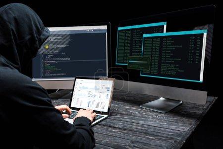 Photo pour Pirate utilisant un ordinateur portable avec des graphiques et des graphiques à l'écran près des écrans d'ordinateur sur noir - image libre de droit