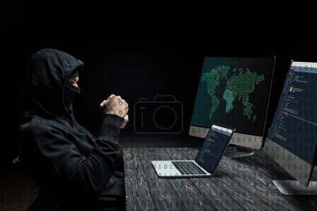 Photo for Hacker with clenched fists looking at laptop with near computer monitors with world map on black - Royalty Free Image