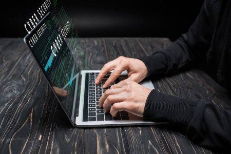 Photo pour Vue recadrée du pirate en utilisant un ordinateur portable avec lettrage de cybersécurité sur noir - image libre de droit
