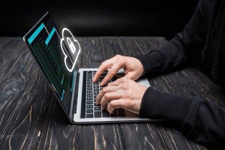 Photo pour Vue recadrée du pirate en utilisant un ordinateur portable avec nuage et cadenas sur noir - image libre de droit