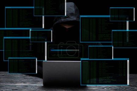 Foto de Hacker in hood usando laptop cerca de pantallas con datos sobre negro. - Imagen libre de derechos