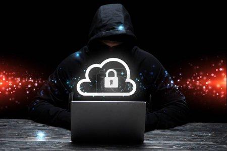 hacker in hood using laptop near cloud with padlock on black
