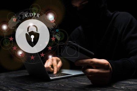 Photo pour Foyer sélectif du pirate dans le masque à l'aide d'un ordinateur portable tout en tenant la carte de crédit près du cadenas avec lettrage gdpr sur noir - image libre de droit
