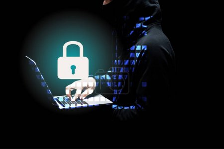 Photo for Cropped view of hacker in hood using laptop near padlock on black - Royalty Free Image