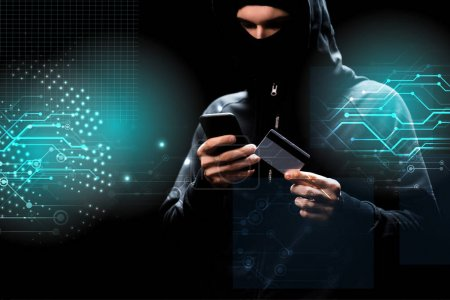 Photo pour Hacker in hood using smartphone and holding credit card near illustration on black - image libre de droit