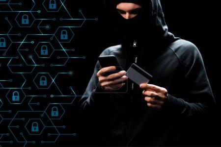 Photo pour Pirate dans le capot en utilisant smartphone et tenant la carte de crédit près de cadenas sur noir - image libre de droit
