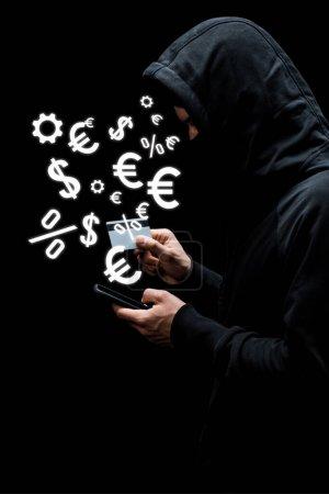Photo pour Pirate dans le capot et le masque à l'aide d'un smartphone et tenant la carte de crédit près de signes d'argent isolé sur noir - image libre de droit