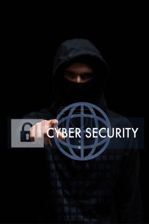 Photo pour Focus sélectif du pirate dans le capuchon pointant avec le doigt à la sécurité cybernétique lettrage sur noir - image libre de droit