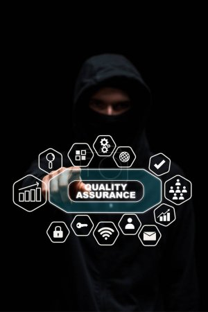 selective focus of hacker in hood pointing with finger at quality assurance lettering on black