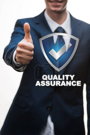 selective focus of happy businessman in suit showing thumb up near quality assurance lettering on white