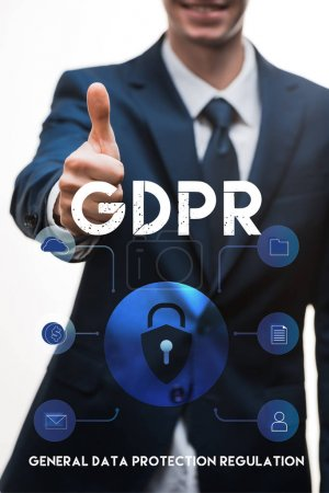 selective focus of happy businessman in suit showing thumb up near gdpr lettering on white