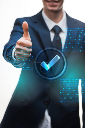 selective focus of happy businessman in suit showing thumb up near check mark on white