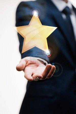 Photo pour Vue recadrée de l'homme d'affaires en costume avec la main tendue près de l'étoile sur blanc, concept de qualité - image libre de droit