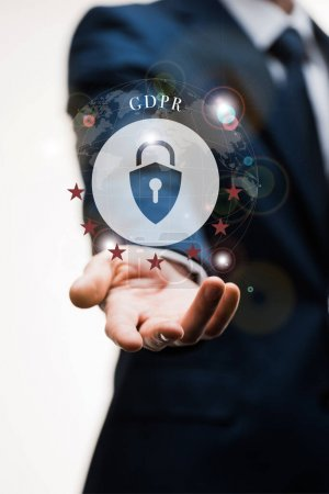 cropped view of businessman in suit with outstretched hand near gdpr lettering on white