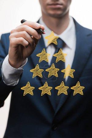 Photo pour Foyer sélectif de l'homme d'affaires en tenue formelle stylo marqueur près des étoiles sur blanc, concept de qualité - image libre de droit