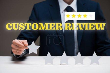 Foto de Vista recortada de hombre de negocios celebración estrella cerca de letras de opinión del cliente en gris, concepto de calidad - Imagen libre de derechos