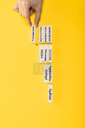Photo pour Vue de dessus de l'homme tenant bloc de bois avec lettrage de travail d'équipe isolé sur jaune - image libre de droit