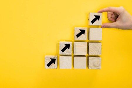 Photo pour Vue de dessus du cube homme tenant avec flèche directionnelle isolé sur jaune, concept de qualité - image libre de droit