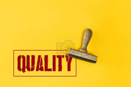 Photo pour Vue du dessus du timbre avec lettrage de qualité sur jaune - image libre de droit