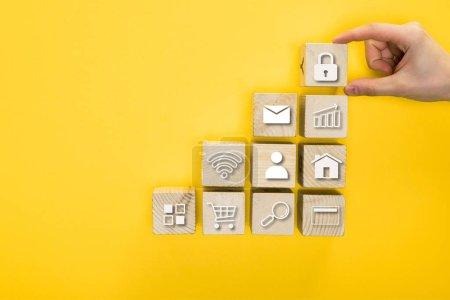 Photo pour Vue de dessus de l'homme tenant cube en bois avec cadenas isolé sur jaune - image libre de droit