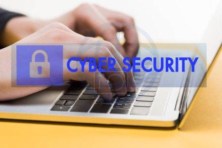 Photo pour Gros plan d'un pirate informatique utilisant un ordinateur portatif près du lettrage de cybersécurité sur blanc - image libre de droit
