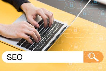 Foto de Vista recortada de hacker usando laptop cerca de la barra de búsqueda con la carta seo. - Imagen libre de derechos