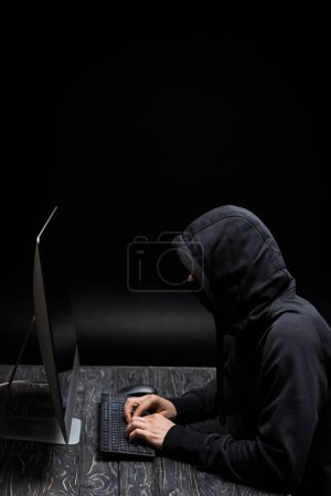 Photo pour Pirate à capuchon dans un masque dactylographie sur clavier d'ordinateur sur noir - image libre de droit