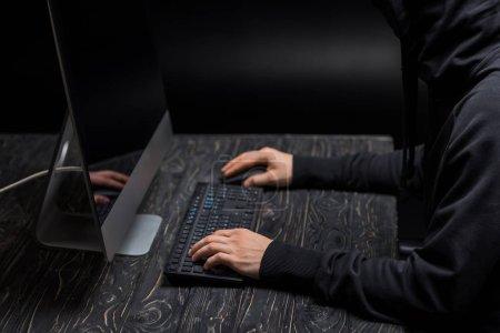 Foto de Vista recortada de hacker tecleando en teclado de computadora en negro. - Imagen libre de derechos