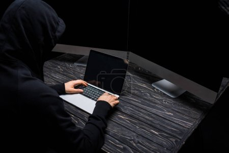 Photo for Hooded hacker using laptop near computer monitors with blank screen isolated on black - Royalty Free Image