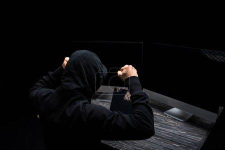 Photo pour Hacker bouleversé avec les poings serrés près des moniteurs d'ordinateur avec écran vide isolé sur noir - image libre de droit