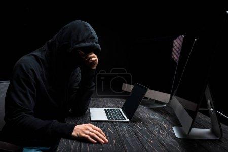 Foto de Hacker molesto sentado cerca de portátiles y monitores de computadora con pantalla en blanco aislado en negro. - Imagen libre de derechos