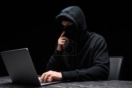 Foto de Joven hacker tocando máscara y utilizando portátil aislado en negro. - Imagen libre de derechos