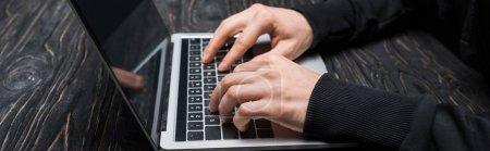 Photo pour Prise de vue panoramique du pirate tapant sur le clavier de l'ordinateur portable - image libre de droit