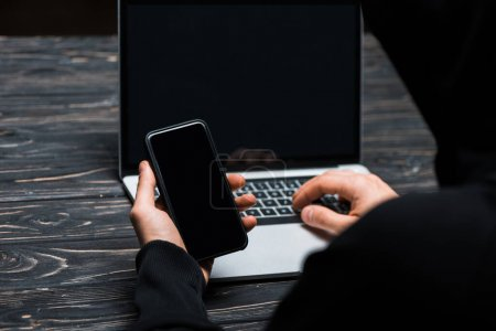 Photo for Cropped view of hacker using smartphone near laptop with blank screen isolated on black - Royalty Free Image