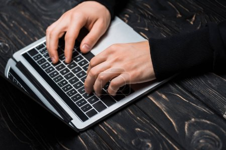 Photo for Cropped view of hacker typing on laptop keyboard - Royalty Free Image