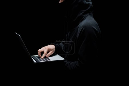 Photo for Cropped view of hacker in hood using laptop isolated on black - Royalty Free Image