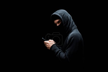 Photo pour Hacker in hood and mask holding smartphone and looking at camera isolated on black - image libre de droit