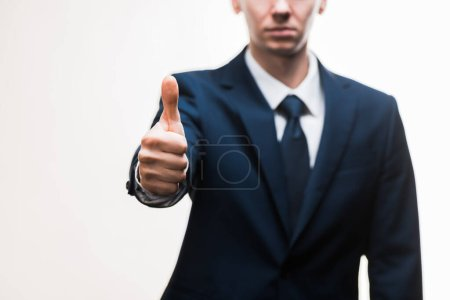selective focus of businessman in suit showing thumb up isolated on white
