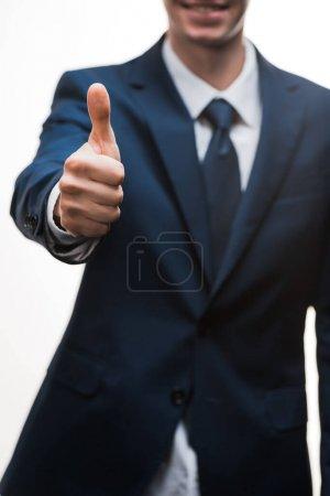 Photo pour Foyer sélectif de heureux homme d'affaires en costume montrant pouce vers le haut isolé sur blanc - image libre de droit