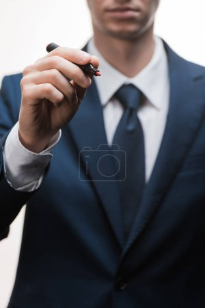selective focus of businessman in formal wear holding marker pen isolated on white