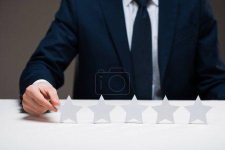 Photo pour Vue recadrée de l'homme d'affaires touchant étoile isolé sur gris, concept de qualité - image libre de droit
