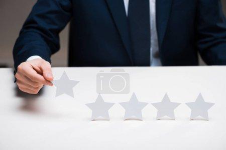 Photo pour Crochet vue d'un homme d'affaires en costume tenant la vedette sur le gris, concept de qualité - image libre de droit