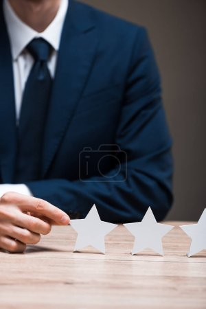 cropped view of man in formal wear touching star isolated on grey, quality concept