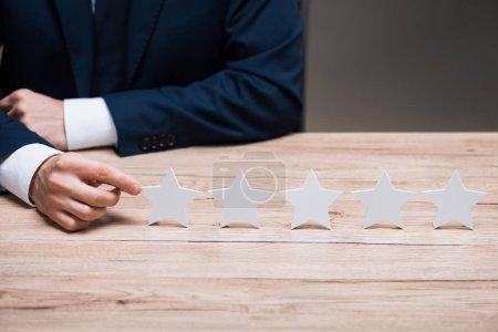 Photo pour Vue recadrée de l'homme dans l'usure formelle pointant avec le doigt à l'étoile isolé sur gris, concept de qualité - image libre de droit