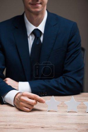 Photo pour Crochet vue d'un homme d'affaires heureux en tenue officielle touchant une étoile isolé sur un concept gris de qualité - image libre de droit