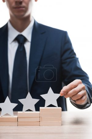 cropped view of businessman touching star isolated on white, quality concept