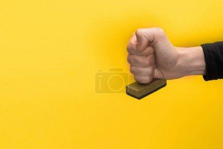 Photo pour Vue recadrée de l'homme tenant le timbre isolé sur jaune, concept de qualité - image libre de droit