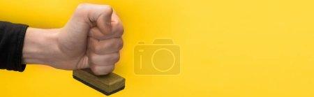 Photo pour Plan panoramique de l'homme tenant le timbre isolé sur jaune, concept de qualité - image libre de droit