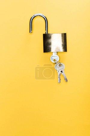 Photo pour Vue de dessus du cadenas métallique avec clés isolées sur jaune - image libre de droit