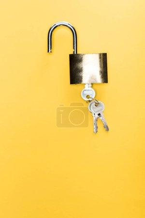 top view of metallic padlock with keys isolated on yellow